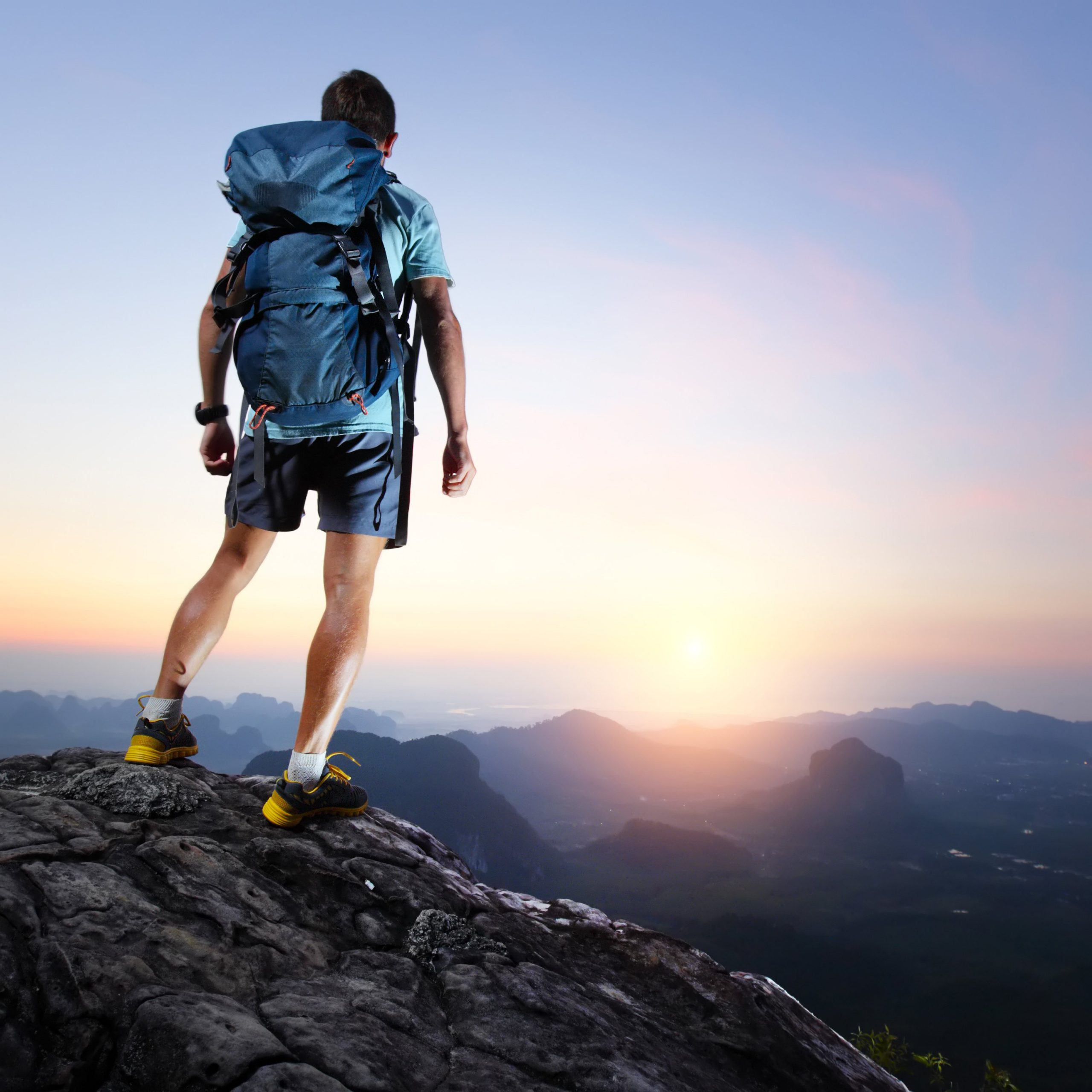 Hiker with backpack standing on top of a mountain and enjoying sunrise